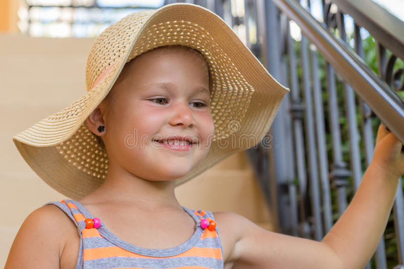 Mała dziewczynka z kapeluszem na schodkach zdjęcia royalty free