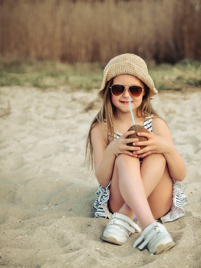 Mała dziewczynka z koksem na plaży przy zmierzchem zdjęcia stock