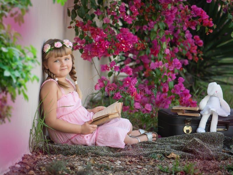 Mała dziewczynka z książką w parku zdjęcia stock