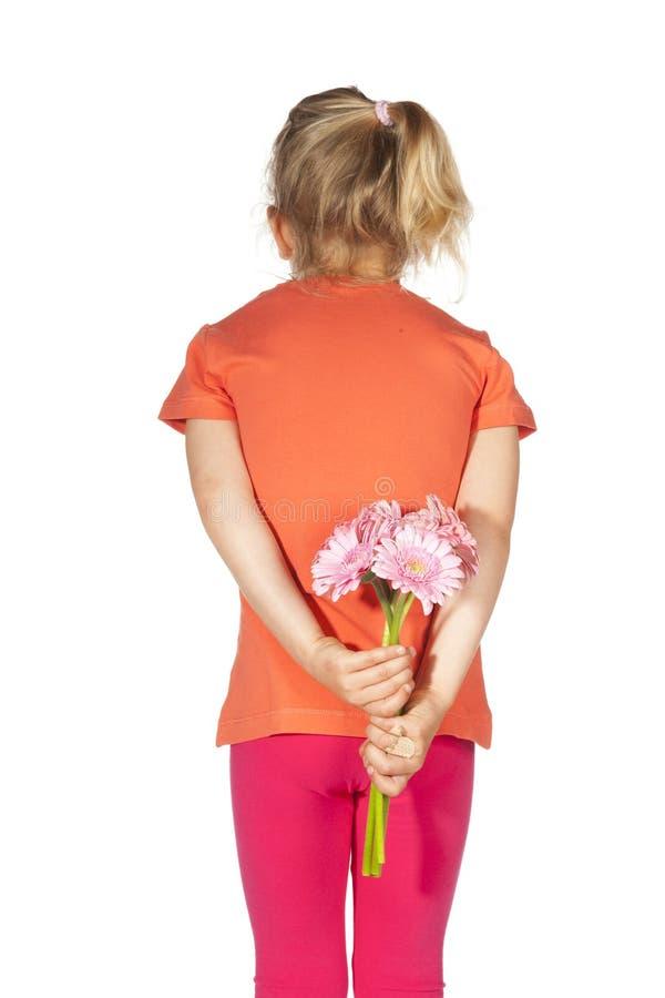 Mała dziewczynka z kwiatami za ona z powrotem zdjęcia stock
