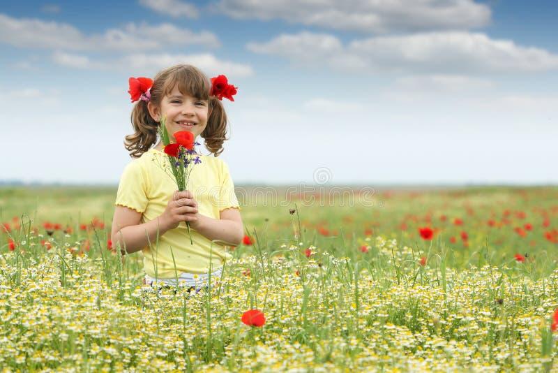 Mała dziewczynka z maczkiem kwitnie na łące obraz stock