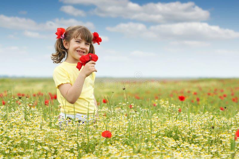 Mała dziewczynka z maczkiem kwitnie na łące obrazy royalty free