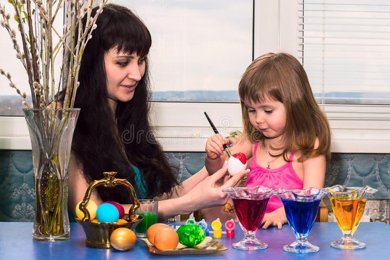Mała dziewczynka z mamą maluje Wielkanocnych jajka przed wakacje obraz royalty free