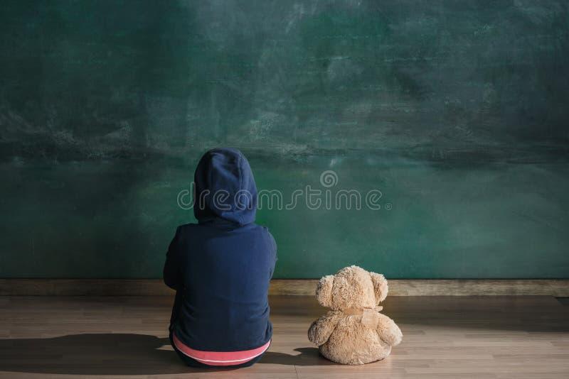 Mała dziewczynka z misiem siedzi na podłoga w pustym pokoju Autyzmu pojęcie obraz stock