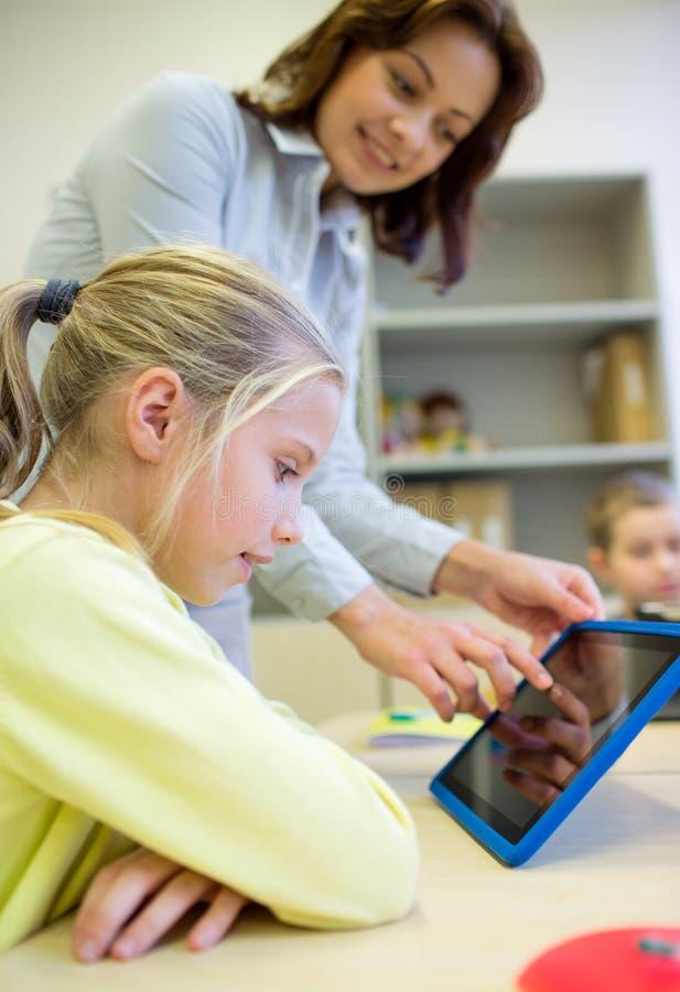 Mała dziewczynka z nauczyciela i pastylki komputerem osobistym przy szkołą obraz royalty free