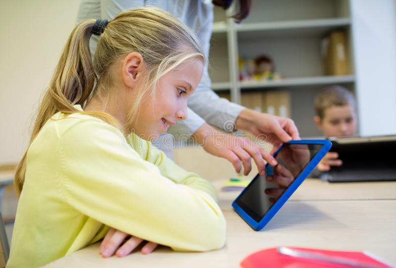 Mała dziewczynka z nauczyciela i pastylki komputerem osobistym przy szkołą obraz stock
