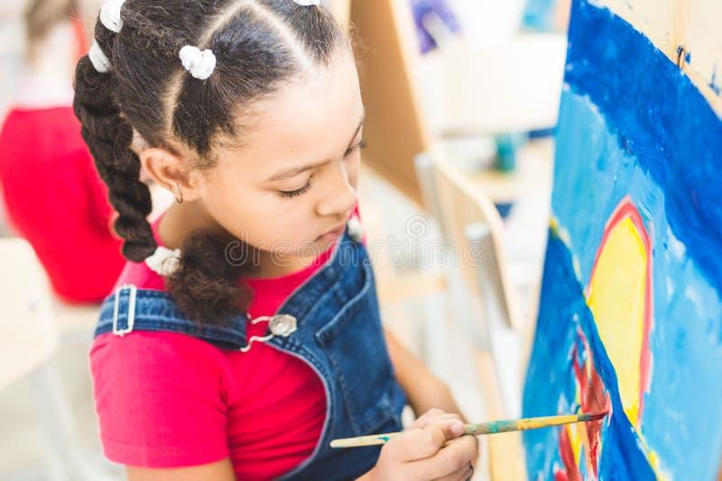 Mała dziewczynka z nauczycielem w grupie preschool uczeń siedział rysunek obrazek Malujący na maelbert, paleta i obrazy royalty free