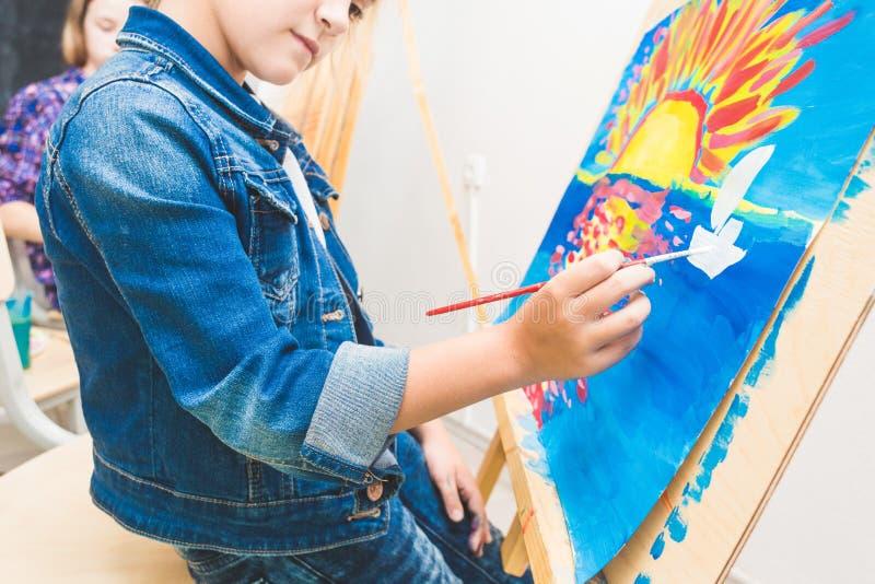 Mała dziewczynka z nauczycielem w grupie preschool uczeń siedział rysunek obrazek Malujący na maelbert, paleta i zdjęcie royalty free