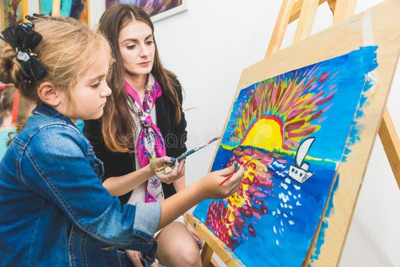 Mała dziewczynka z nauczycielem w grupie preschool uczeń siedział rysunek obrazek Malujący na maelbert, paleta i obraz royalty free