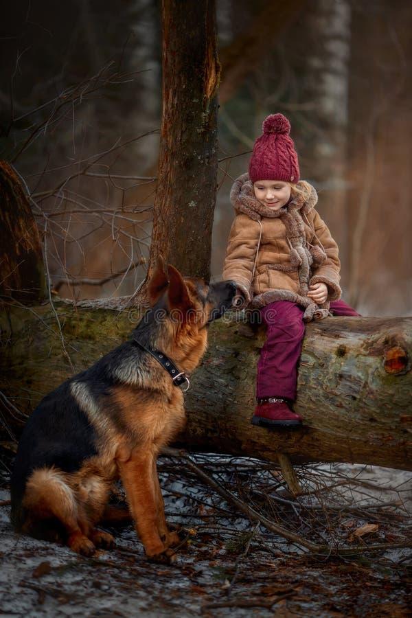 Mała dziewczynka z Niemieckiej bacy 6 th miesięcy szczeniakiem przy wczesną wiosną obraz royalty free