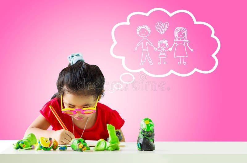 Mała dziewczynka z ołówkowym główkowaniem o rodzinie zdjęcie stock