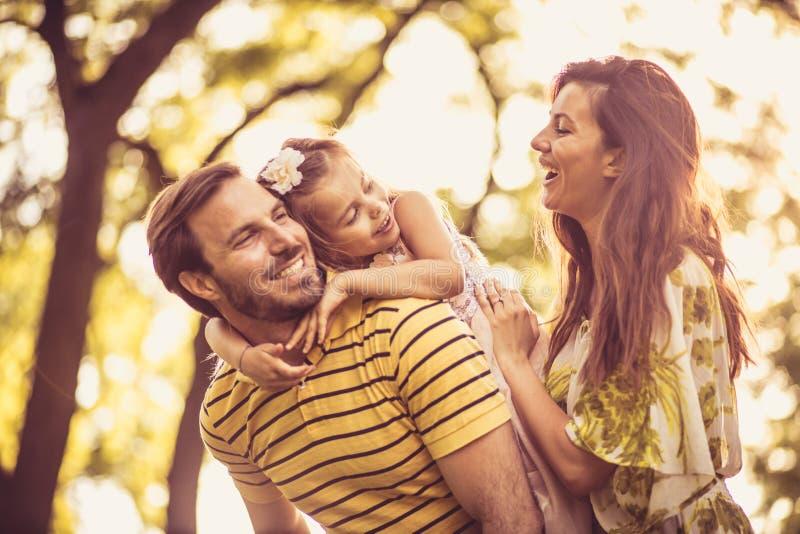Mała dziewczynka z ona rodzice cieszy się w naturze Portret fotografia stock
