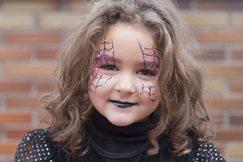 Mała dziewczynka z pająk siecią malującą na twarzy fotografia royalty free