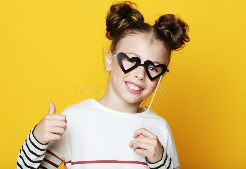 Mała dziewczynka z papierowi akcesoria nad żółtym tłem fotografia royalty free