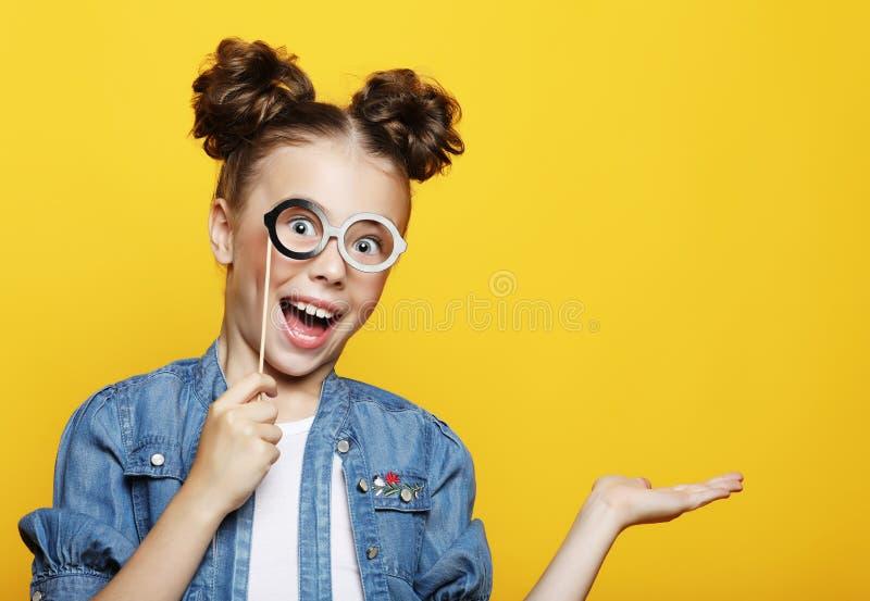 Mała dziewczynka z papierowi akcesoria nad żółtym tłem obrazy stock