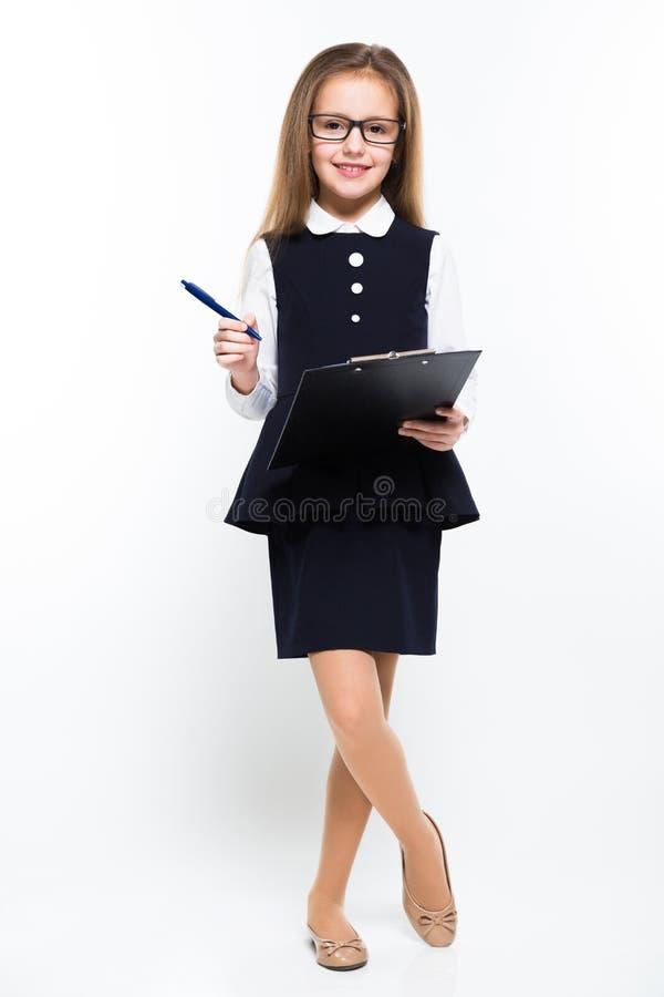 Mała dziewczynka z piórem i schowek w jej rękach ubieraliśmy jako bizneswoman obraz royalty free
