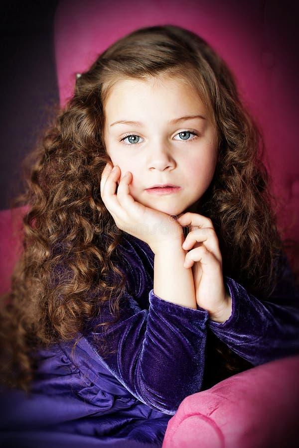 Mała dziewczynka z pięknym włosy pozuje w krześle zdjęcia royalty free