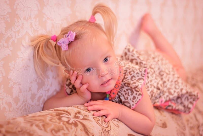 Mała dziewczynka z pigtails kłamstwami zdjęcie stock