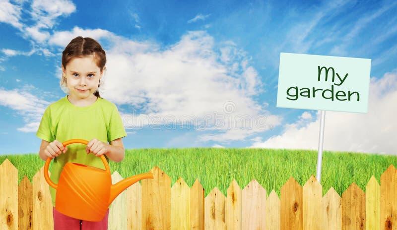 Mała dziewczynka z podlewanie puszką obok ogrodzenia ogród zdjęcia stock