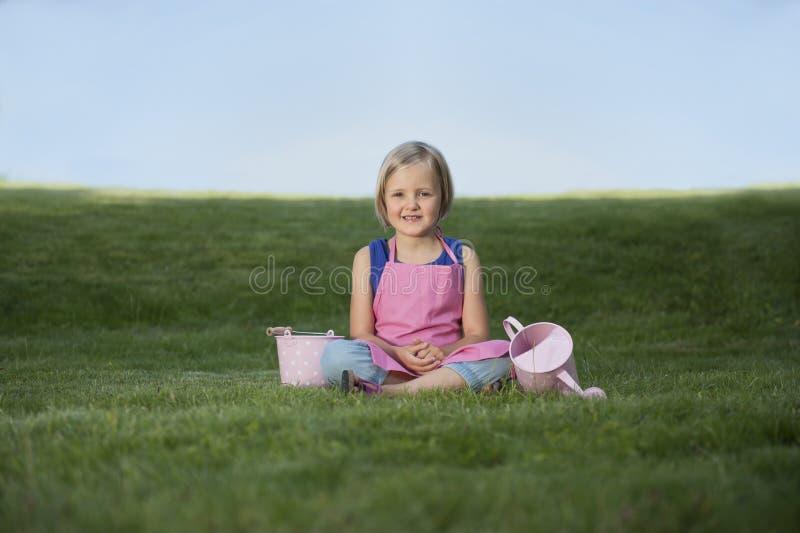 Mała dziewczynka z podlewanie puszką w ogródzie zdjęcia stock