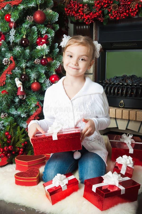 Mała dziewczynka z prezentami zbliżać choinki obraz stock