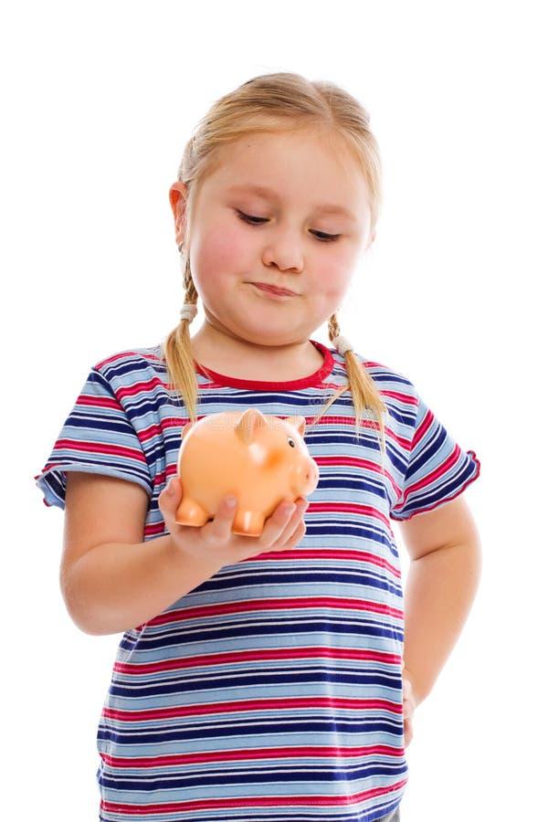 Mała dziewczynka z prosiątko bankiem zdjęcie royalty free