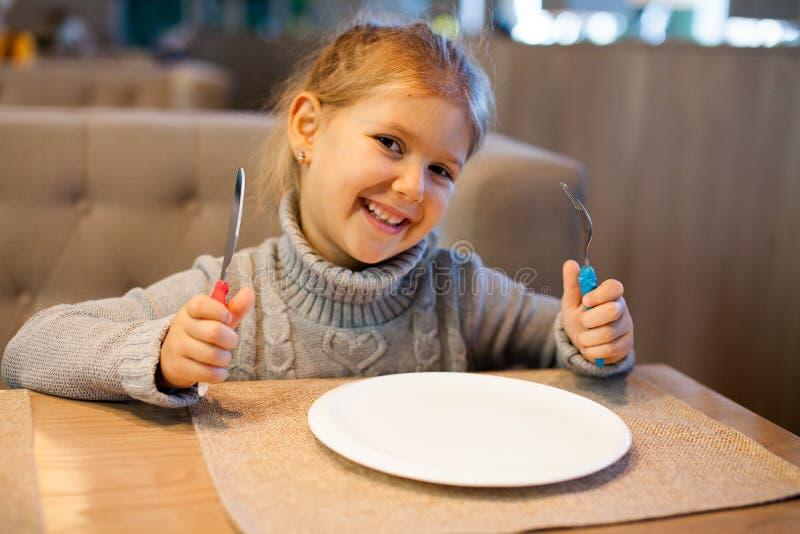Mała dziewczynka z pustym talerzem w restauracji zdjęcia royalty free