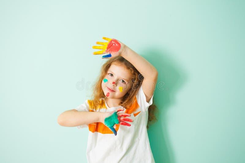 Mała dziewczynka z rękami i twarzą w farbie obraz stock