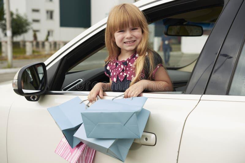 Mała dziewczynka z robić zakupy przyglądający out samochodowy okno fotografia royalty free