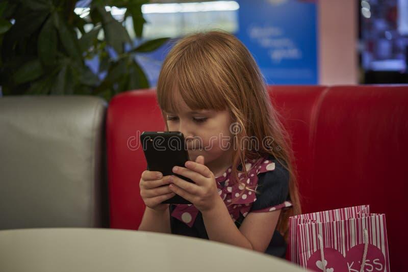 Mała dziewczynka z smartphone w kawiarni obrazy stock