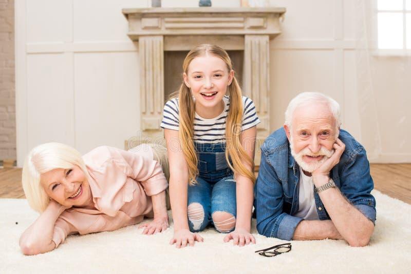 Mała dziewczynka z uśmiechniętym dziaduniem i babcią odpoczywa wpólnie w domu zdjęcia royalty free