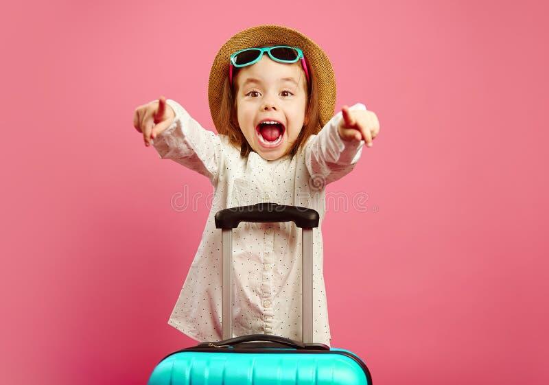 Mała dziewczynka z walizką wyraża niespodziankę i szok, rozpieczętowany jej usta szeroki, jest ubranym plażowego kapelusz i okula obraz royalty free