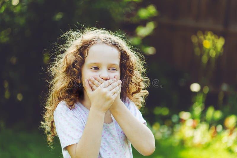 Mała dziewczynka zakrywa jej usta z ona ręki Zdziwiony lub blizno obraz stock