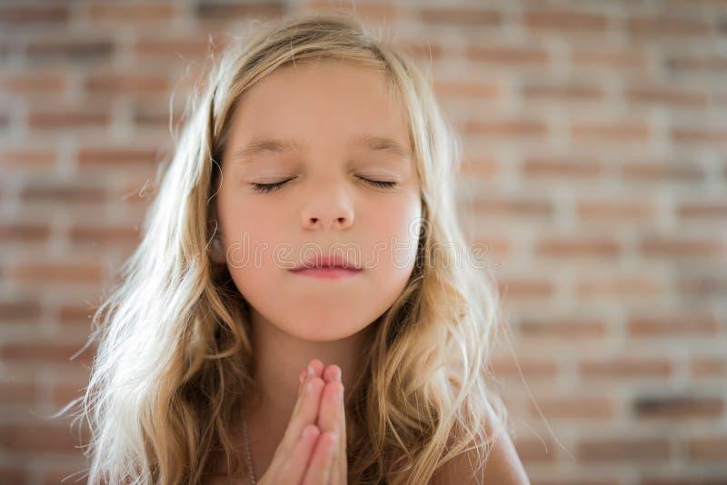 Mała dziewczynka zamykał ona i ono modli się oczy zdjęcie stock
