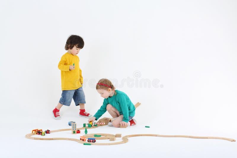 Mała entuzjastyczna dziewczyna i chłopiec bawić się z drewnianą koleją zdjęcie stock
