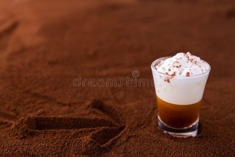 Mała filiżanka flecika latte macchiato na stole zakrywającym z strzałą na zmielonej kawie jako tło zdjęcie stock