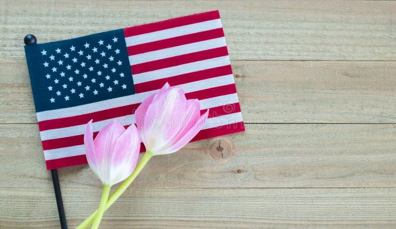 Mała flaga amerykańska z różowymi tulipanami na drewnianym tle obrazy stock