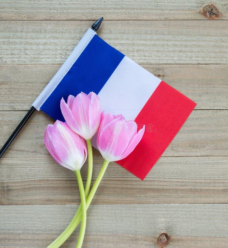 Mała francuz flaga z różowymi tulipanami na drewnianym tle zdjęcia royalty free