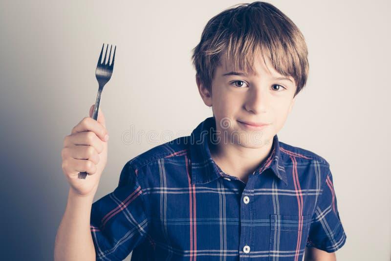 Mała głodna chłopiec z rozwidleniem przygotowywającym jeść obrazy royalty free