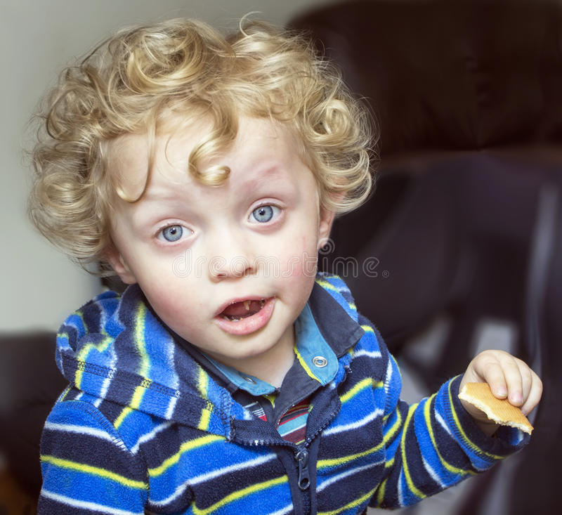Mała kędzierzawa blondynki chłopiec z ciastkiem zdjęcie stock