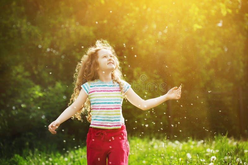 Mała kędzierzawa dziewczyna cieszy się latającego dandelion w zmierzchu świetle Instag zdjęcie royalty free