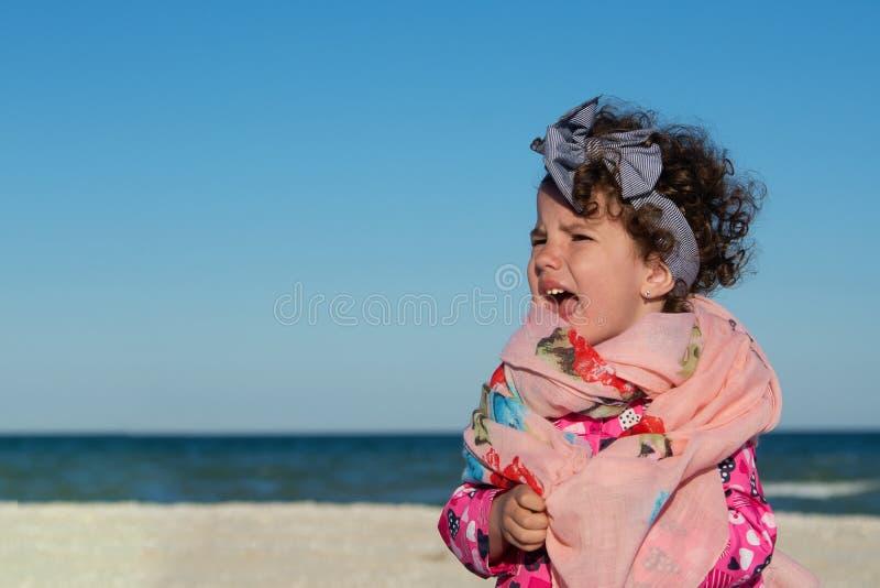 Mała kędzierzawa dziewczyna krzyczy i jest zgrymaszony przy denną plażą zdjęcie royalty free