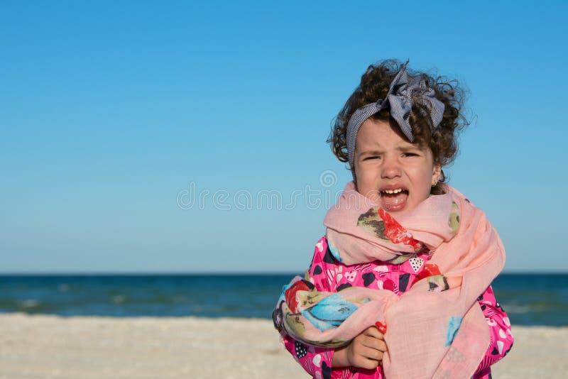 Mała kędzierzawa dziewczyna krzyczy i jest zgrymaszony przy denną plażą zdjęcie stock