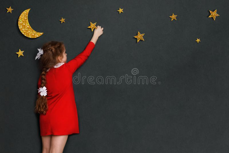 Mała kędzierzawa dziewczyna w czerwieni sukni dosięga out dla gwiazd i m obraz stock