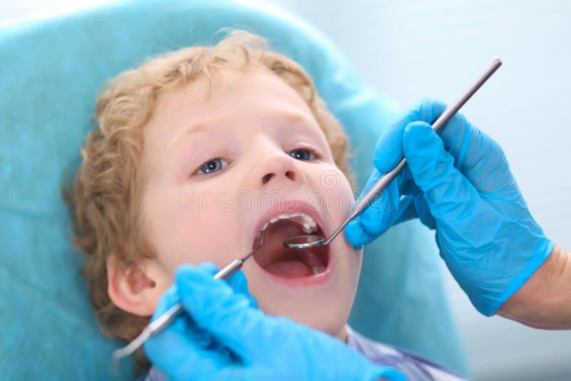 Mała kędzierzawa Kaukaska chłopiec otwiera jego usta szerokiego podczas inspekci oralny zagłębienie dentystą fotografia royalty free