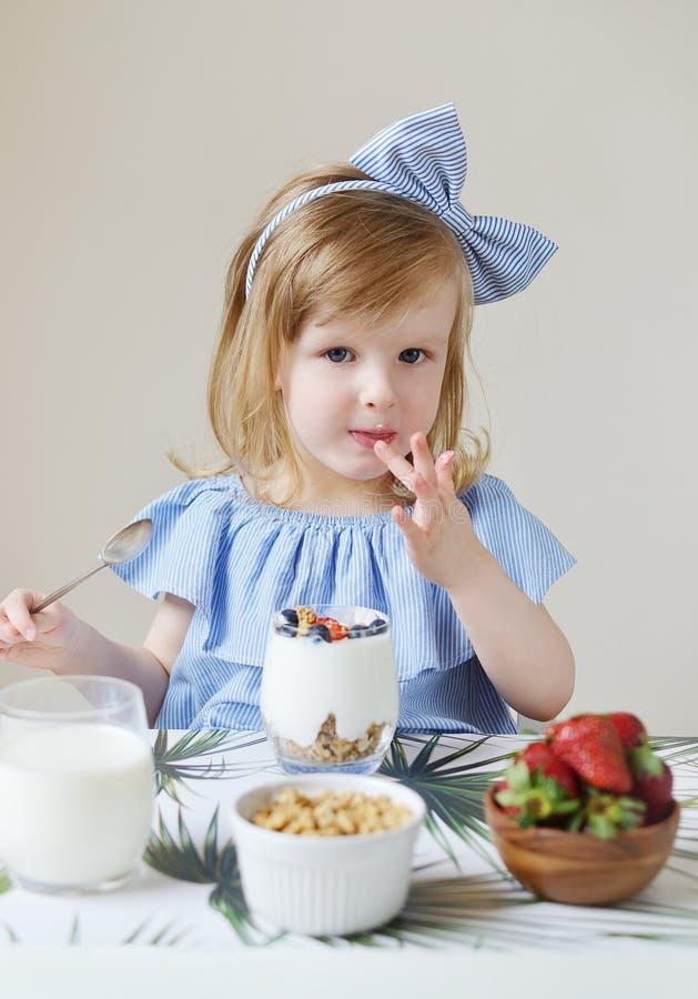 Mała Kaukaska Blond dziewczyna Je Zdrowej śniadania mleka jagod Truskawkowej czarnej jagody Greckiego jogurt z Muesli dietą w dom zdjęcie royalty free