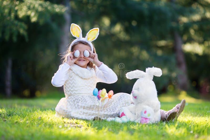 Mała Kaukaska dziewczyna w świątecznym obsiadaniu na zielonej trawie i bawić się z sukni i królików ucho kapitałki Wielkanocnymi  obraz stock