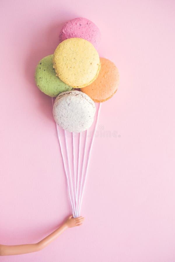 Mała klingeryt zabawki ręka trzyma stubarwnego macaron szybko się zwiększać na pastelowych menchii tła abstrakta pojęciu zdjęcie stock