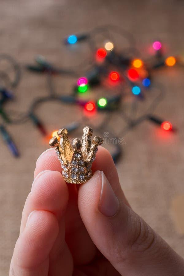 Mała korona w ręce z światłami behind obraz stock