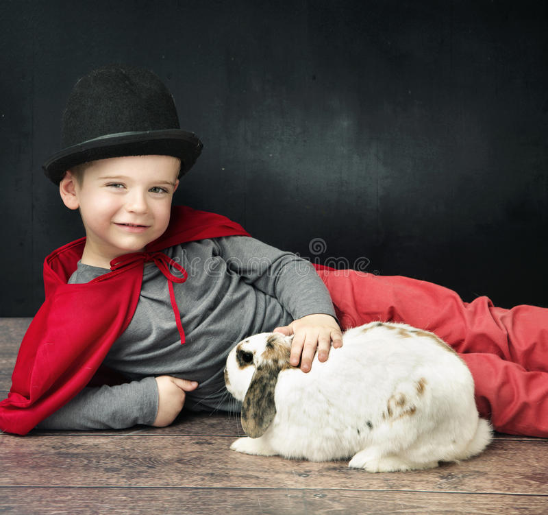 Mała magik chłopiec muska królika fotografia royalty free